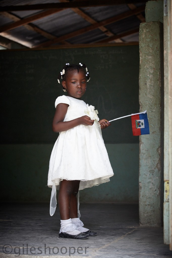 A Little girl plays with her flag in a small mountain school near Montrouis, Haiti